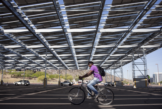 A cyclist pedals through a solar panel covered parking lot on the Arizona State University campus.