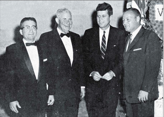 """Eloy farmer Augustus Battaglia, from left, poses with Arizona Gov. Ernest McFarland, U.S. Sen. JohnF. Kennedy, D-Mass., and Arizona Democratic Chairman Joseph Walton in February 1958 at a party in Tucson. The photo provided to the Dispatch after Kennedy's death in 1963 was signed """"To Gus Battaglia, with very warmest regards, John Kennedy."""" / Dispatch (1963)"""