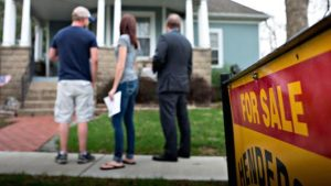 An agent, right, stands with potential home buyers outside a previously owned home in Mackinaw, Illinois. : Daniel Acker | Bloomberg | Getty Images